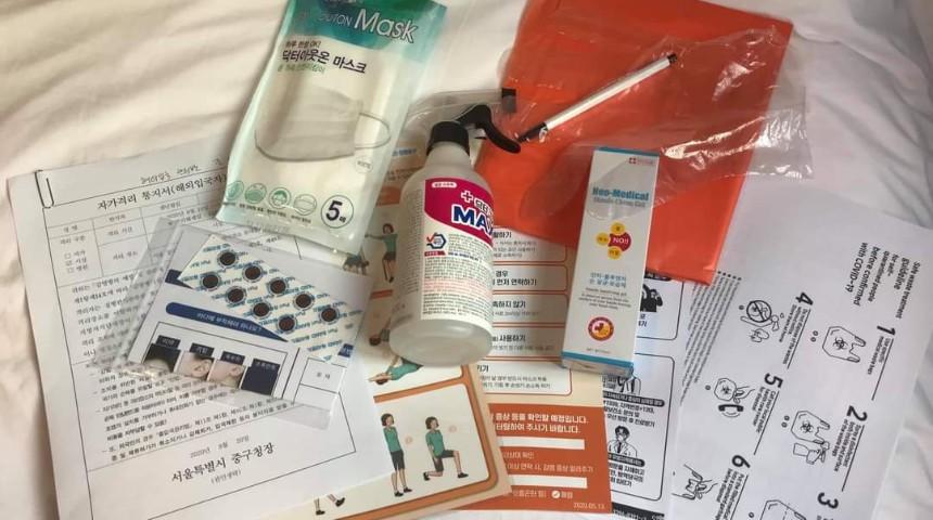 Il Kit Covid-19 distribuito in Corea, con mascherine, gel per le mani, spray antibatterico, termometro adesivo, riviste, una lista di esercizi da fare in stanza o in casa e frutta