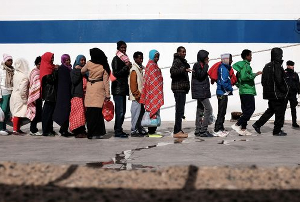 Immigrati in fila con abiti colorati