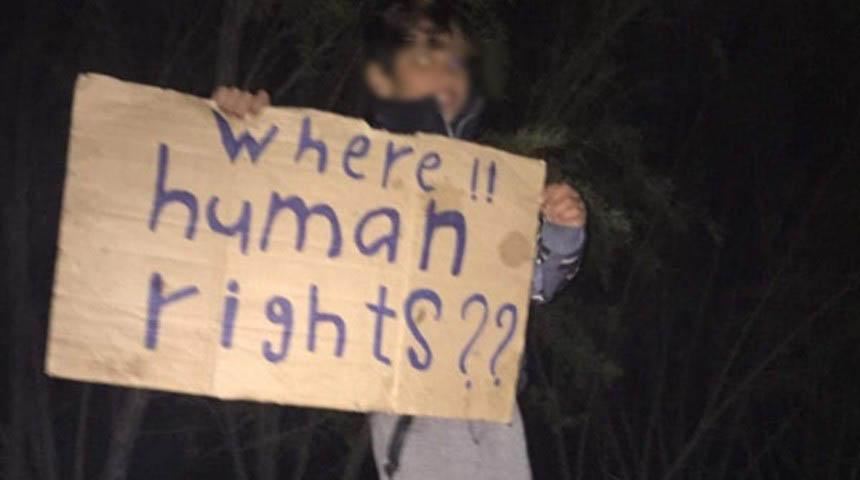 Un bambino ospite dell'Hotspot con un cartello