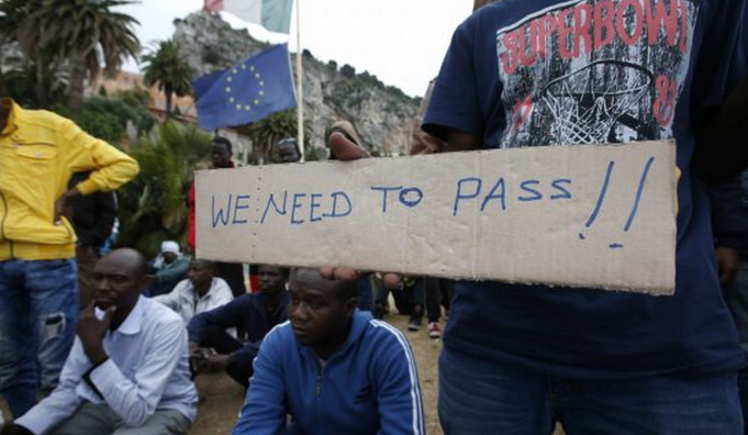 "Migranti Ue - immigrati con scritta ""we need to pass"""