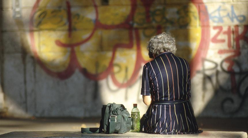 Povertà. Anziana di spalle seduta su un muretto